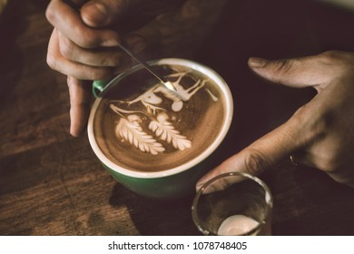 Barista use tiny metal pin draw latte art with white milk on coffee surface