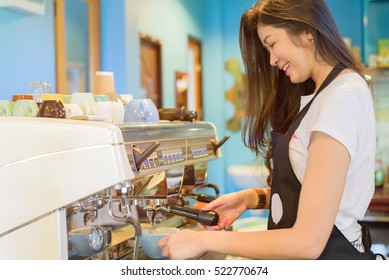 Barista using coffee machine in counter - young Asian woman successful in small business owner food and drink cafe