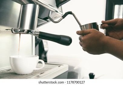 Barista using coffeemaker extraction for espresso shot and steam milk in cafe.