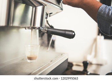 Barista using coffeemaker extraction for espresso shot in cafe.