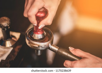 Barista's hands with tamper. Barista compresses coffee grounds with tamper. Making coffee process.