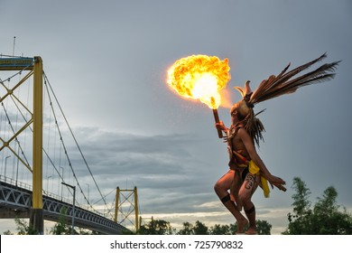 Barito river, Banjarmasin, South Kalimantan, Indonesia - September 23, 2017 : Young man from the Central Kalimantan Dayak tribe performing fire spitting
