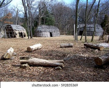 Bark-covered wigwams seen beyond a fire circle at a reconstructed Native American village in Maryland, home to the Nanticoke, Shawnee, Piscataway, Lenape, Tuscarora, and Susquehannock nations.