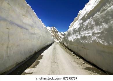 Barlachala pass in Leh Manali Highway, roads through ice walls with snow peak of himalaya in background