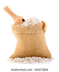 Barley grains in bag on white background