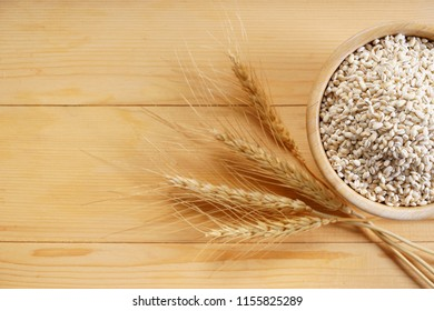 Barley grains in wooden bowl on wooden background