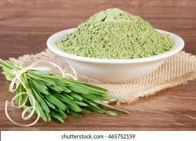 Barley grass with heap of young powder barley in glass dish on jute canvas, wooden background, healthy nutrition and lifestyle, body detox
