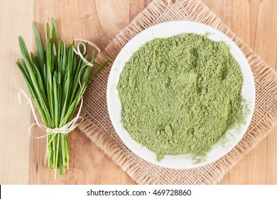 Barley grass with heap of young powder barley in glass bowl on jute canvas, wooden background, healthy nutrition and lifestyle, body detox