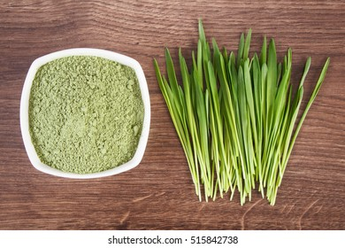 Barley grass with heap of young powder barley in glass dish on wooden background, healthy nutrition and lifestyle, body detox