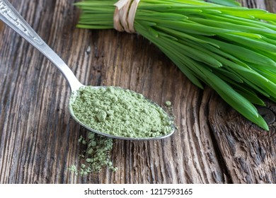 Barley grass powder with freshly harvested blades in the background