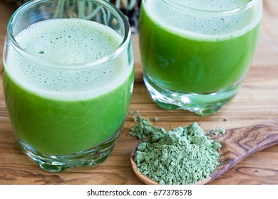 Barley grass powder on a spoon, with two fresh barley grass shots