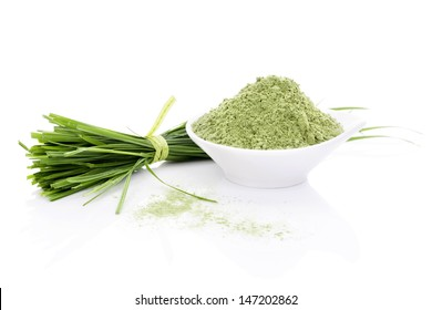 Barley Grass and Wheatgrass. Blades and powder isolated on white background. Green foods. Natural organic healthy living.