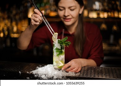 barmaid completes the design of the mojito alcohol cocktail in a glass beaker, adding slice of lime with the tongs