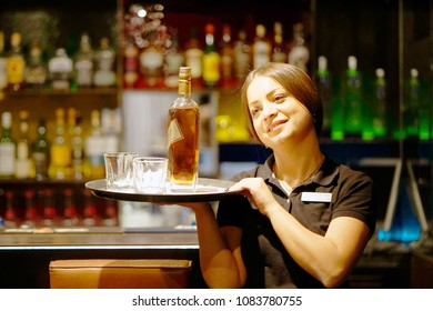 A barmaid girl carries a bottle of whiskey on a tray to the client of the hotel bar. The concept of service. Toning