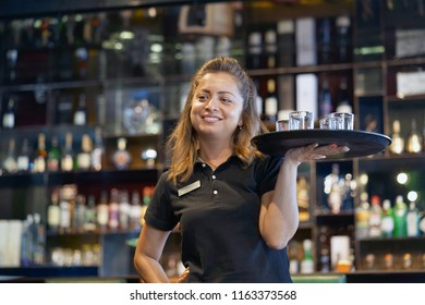A barmaid girl carries glasses fore whiskey on a tray to the client of the hotel bar. Emotion sozheleniya and resentment. The waitress gives a glass fore whiskey. The concept of service.
