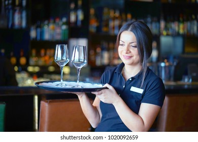 A barmaid girl carries a wine glasses on a tray to the client of the hotel bar. The concept of service.