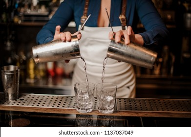 Barmaid pouring fresh alcoholic summer cocktail from shakers into two glasses on the bar counter