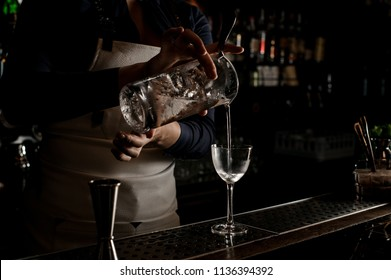 Barmaid pouring fresh summer drink into an elegant cocktail glass on the dark bar counter