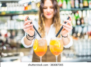 Barmaid preparing cocktails in a bar for her clients - Bartender at work in a club