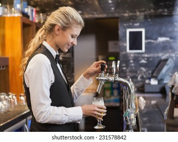 Barmaid pulling a glass of beer in a bar