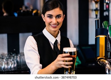 Barmaid serving a pint in a bar