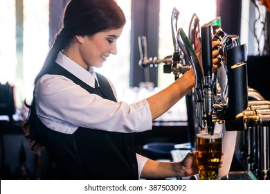 Barmaid serving a pint in a bar