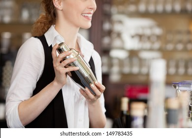 Barmaid shaking a cocktail shaker as she stands behind the bar mixing a drink for a client