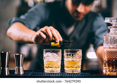 Barman adding cocktail ingredients on whiskey cocktails on bar counter