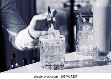 Barman is adding an ice cube to the cocktail with pincers, blue tone monochrome