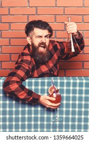 Barman advice concept. Man in checkered shirt near bottle, brick wall and blue tablecloth background. Barman with beard on shouting face holds cocktail. Bartender recommends to try beverage.