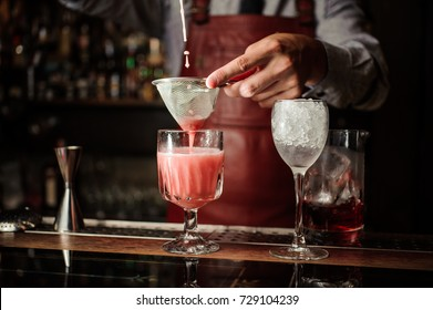 Barman in apron is making alcoholic cocktail at the bar counter on the dark background