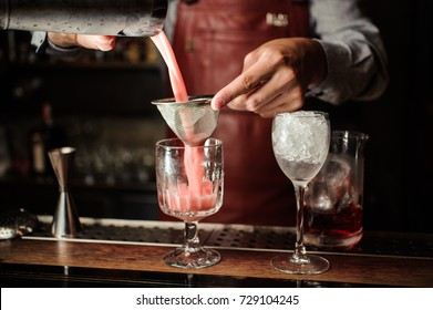 Barman in apron is making an alcoholic cocktail at the bar counter on the dark background
