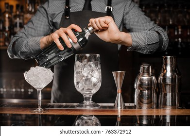 Barman in the apron making a cocktail with help of special bar equipment on the bar counter