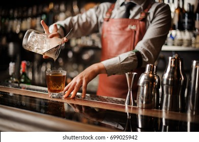 Barman in bar interior making alcohol cocktail. Professional bartender pours drink with a strainer