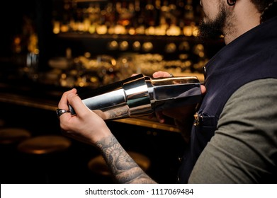 Barman with beard and tattoo on his hand making fresh and tasty alcoholic summer cocktail in professional shaker