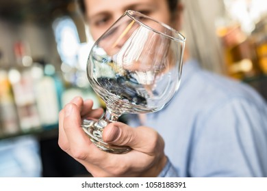 Barman Checking the Clarity of a Glass in Bar