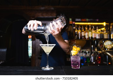 The barman creates beautiful alcoholic cocktails at the bar. The barman pours out the ingredients from the shaker.alcoholic cocktail.