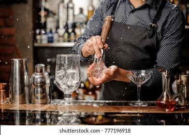 Barman crushing a big piece of ice on the bar counter with a special bar equipment on it for a cocktail