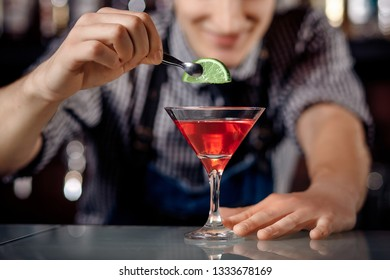 Barman decorates lime cocktail in martini glass.