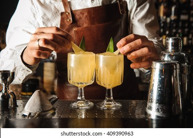 Barman is decorating cocktail with lemon no face