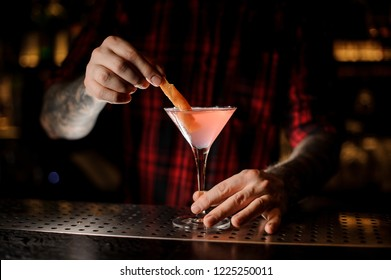 Barman decorating fresh Cosmopolitan cocktail with an orange peel on the dark background of bar
