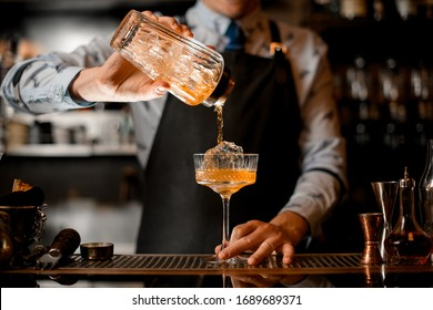 barman gently pours finished cocktail from glass shaker into glass. Body of bartender in black apron on background.