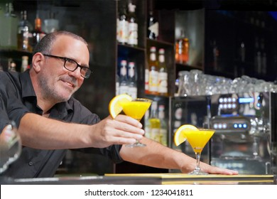 The barman gives a cocktail to the client of the hotel bar. Fresh yellow cocktail with orange. Alcoholic, non-alcoholic drink-beverage at the bar counter in the night club. Glass of orange cocktail.