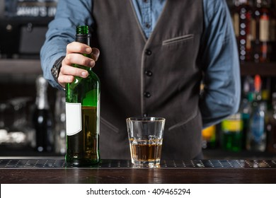 Barman giving whiskey glass with booze and bottle- concept image.