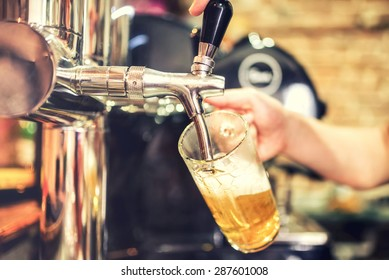barman hand at beer tap pouring a draught lager beer serving in a restaurant or pub. Vintage soft effect on photo