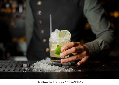 Barman hand holding a glass filled with fresh and cool Caipirinha cocktail on the bar counter