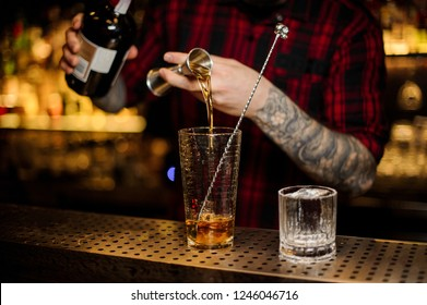 Barman hand pouring strong alcohol into a cocktail glass using a professional bartender tool on the bar