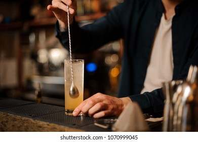Barman hand stirring a fresh and sweet orange summer cocktail with a spoon on the bar counter