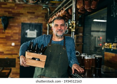 barman holding beers in wooden crate in bar
