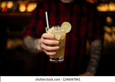 Barman holding a glass of fresh sour and sweet mojito cocktail with lime and lemon slices and straw